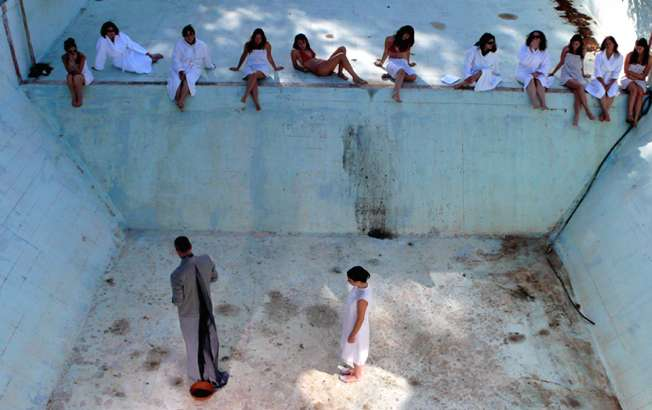 photo of woman dressed in white following a man dressed in grey in an empty pool with a row of bathing women spectating from above